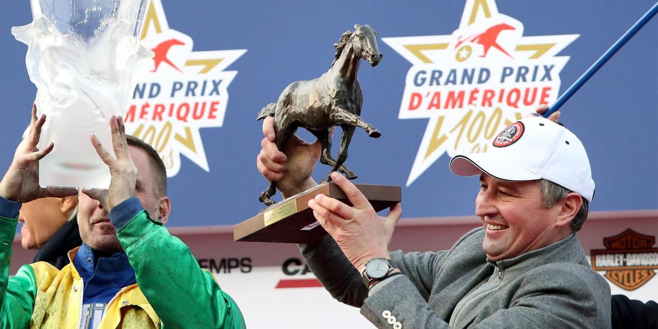 Face Time Bourbons tränare Sébastien Guarato fick för tredje gången de senaste fem åren kliva upp på segrarens podium efter Prix d'Amériqiue. Foto Mia Törnberg/Sulkysport